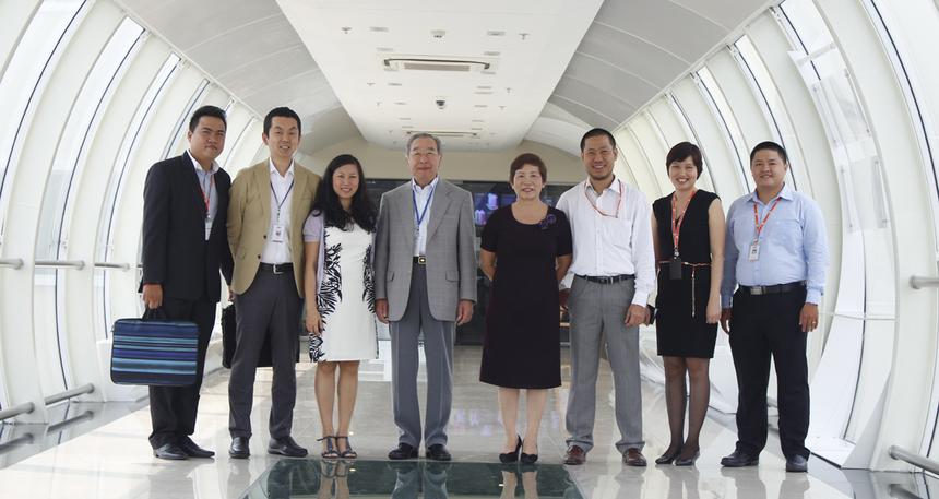 """Cùng chụp hình lưu niệm tại cây cầu nối tòa nhà F-Town1 và F-Town2. Bác Hamaguchi nguyên là Chủ tịch kiêm CEO của NTT Data - công ty dịch vụ CNTT lớn thứ 6 toàn cầu (từ 2003-2007). NTT Data trực thuộc NTT Group của Nhật Bản, tập đoàn đứng thứ 32 trong danh sách 500 công ty lớn nhất thế giới của Fortune (Fortune Global 500) năm 2013. Tại Nhật Bản, Tomokazu Hamaguchi là một """"cây đa cây đề"""" trong lĩnh vực CNTT với trên 40 năm kinh nghiệm."""