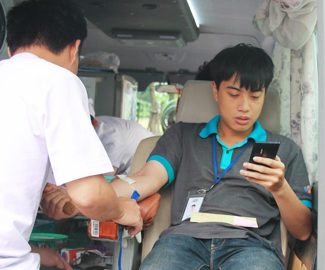 Vừa tranh thủ hiến máu vừa kiểm tra e-mail công việc đầu ngày.