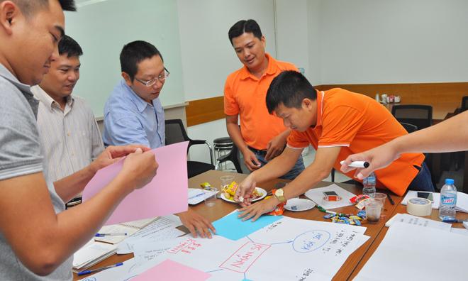 Sau khi hoàn thành bài làm, nhóm 3 còn dán các nội dung chính để bảo mật va tạo hiệu ứng bất ngờ khi trình bày. Các giám đốc chi nhánh đi kiếm giấy màu và băng dính để dán lại. 3 hàng chữ được chừa ra là từ khóa của chương trình: Chiến lược - Niềm tin - Sự khác biệt.