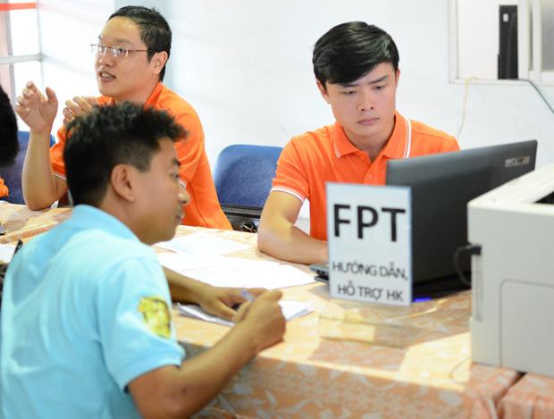 Anh Nguyễn Văn Thống (ngoài cùng bên phải) hướng dẫn hành khách đặt vé qua mạng.