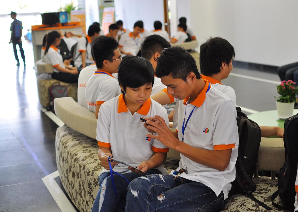 Diệp Lâm Minh Thư (trái), sinh viên FPT, là một trong 5 thí sinh nữ tham gia teambuilding. Trong khi chờ ở sảnh, Thư và bạn cùng nhóm FIT đang tranh thủ trao đổi đề tài dự thi.