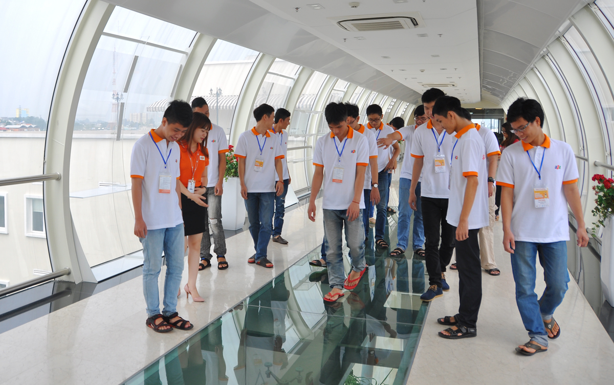 Ngay sau đó, đoàn chia làm hai nhóm tham quan F-Town, nơi làm việc của gần 3.000 lập trình viên. Ảnh: Các sinh viên thích thú với lối đi bằng kính tại cây cầu nối tòa nhà F-Town 1 và F-Town 2 ở độ cao gần 20m.