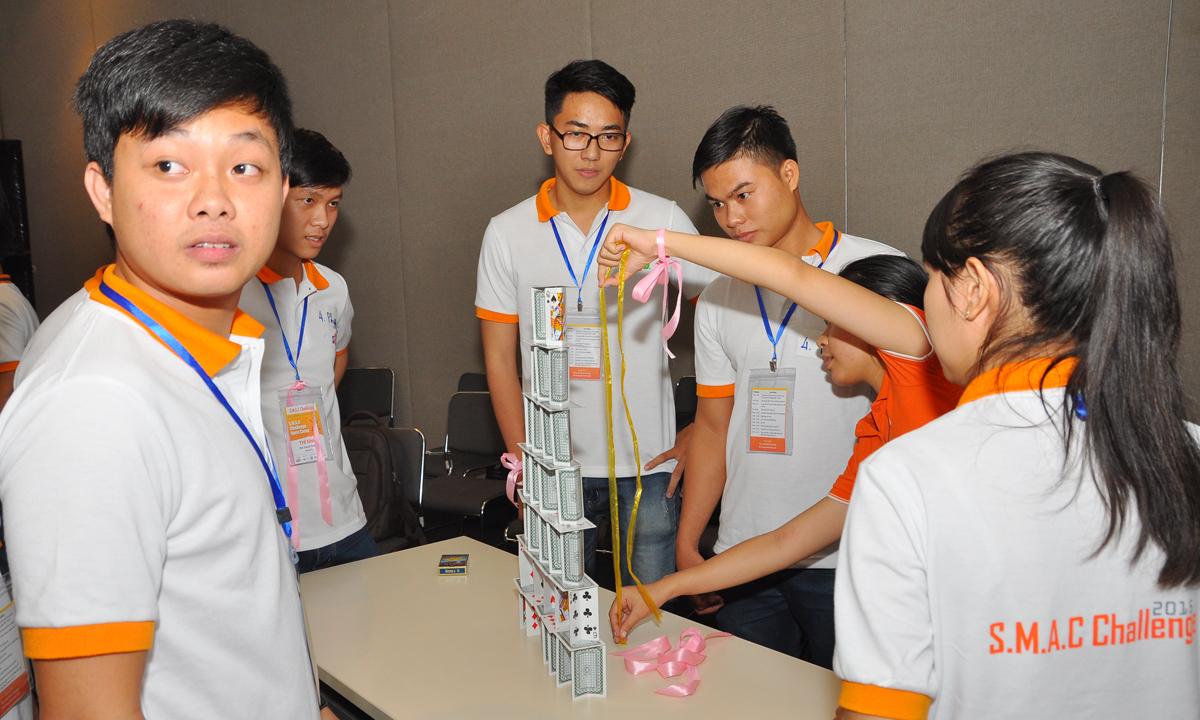 Trong khi trọng tài đo chiều cao của tháp, bạn Vũ An Khang (góc trái), đội AWI của ĐH CNTT TP HCM, nhưng hiện thuộc biên chế nhóm 4 nhìn sang đội bạn với vẻ mặt lo lắng.