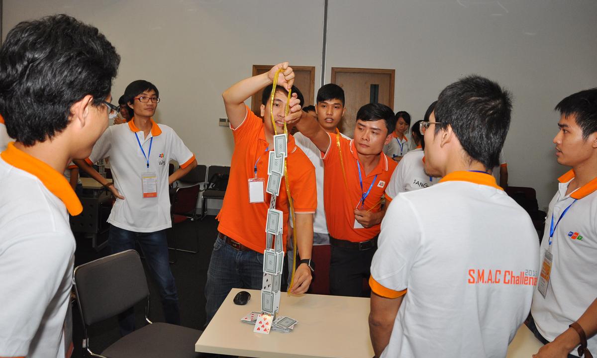 Trọng tài Lê Ngọc Tuấn và Đặng Văn Thống cẩn thận đo tháp của đội 7. Đội này chọn cách xé lá bài và dính vào nhau để tạo sự chắc chắn.