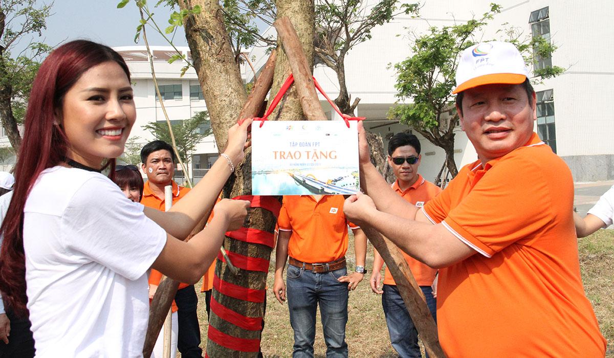 Chủ tịch FPT Trương Gia Bình và Top 25 Hoa hậu Thế giới 2014 Nguyễn Thị Loan gắn biển trao tặng cây xanh.