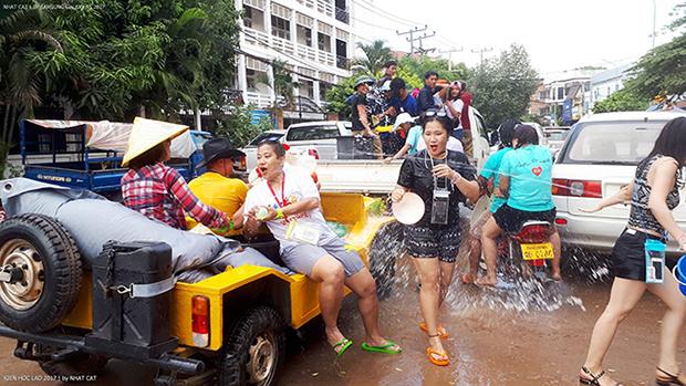 """Tết cổ truyền của người Lào diễn ra từ ngày 14 đến ngày 16/4 hàng năm và """"té nước"""" là hoạt động truyền thống không thể thiếu của người Lào. Nguyễn Quỳnh Anh và Lê Ngọc Quỳnh, 2 cán bộ văn hoá FPT phấn khích tạt nước người đi đường"""
