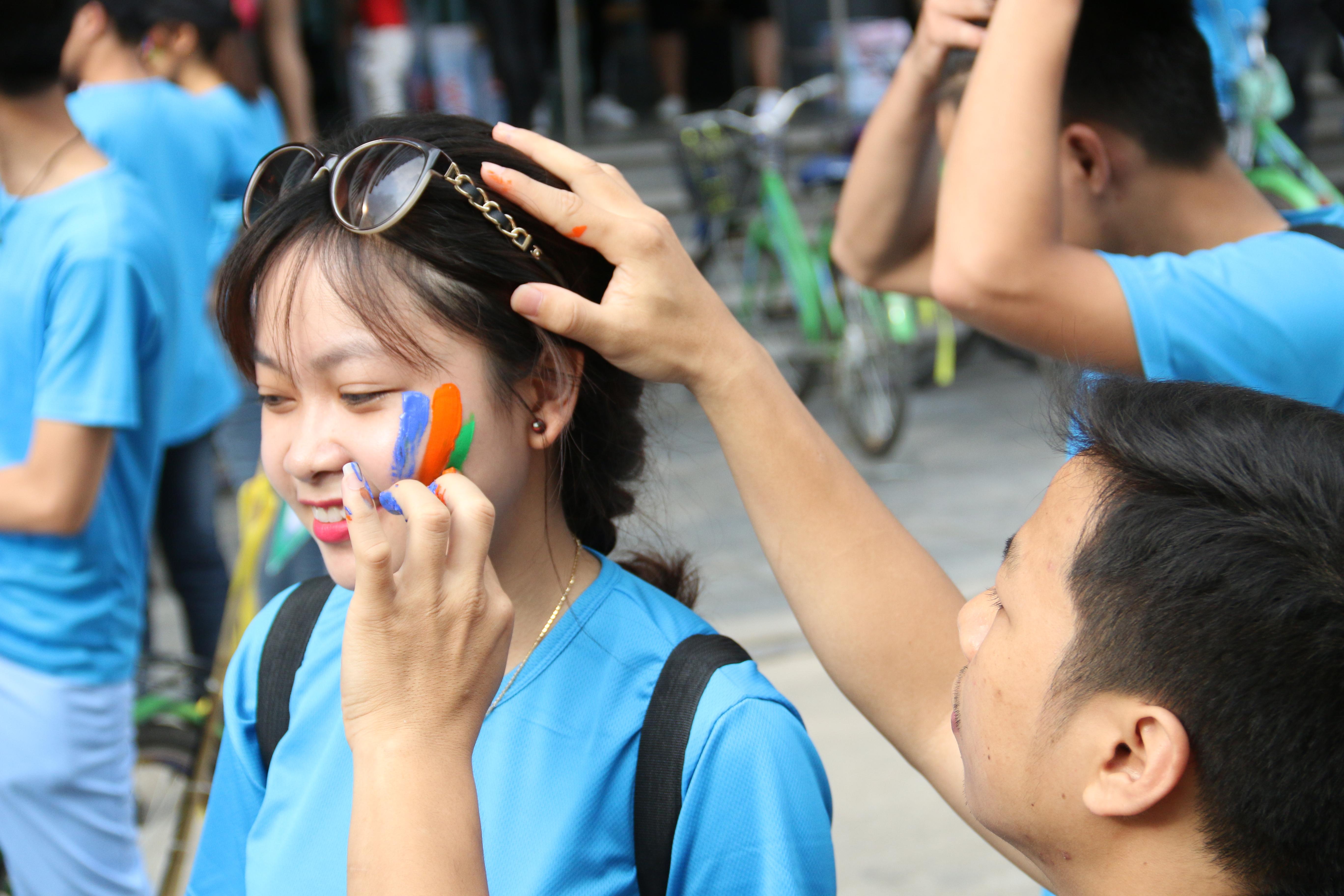 Mọi người hồ hởi nhận đồng phục, trang trí cho xe đạp và tự tay vẽ lên mặt logo FPT trước khi cuộc đua chính thức bắt đầu.
