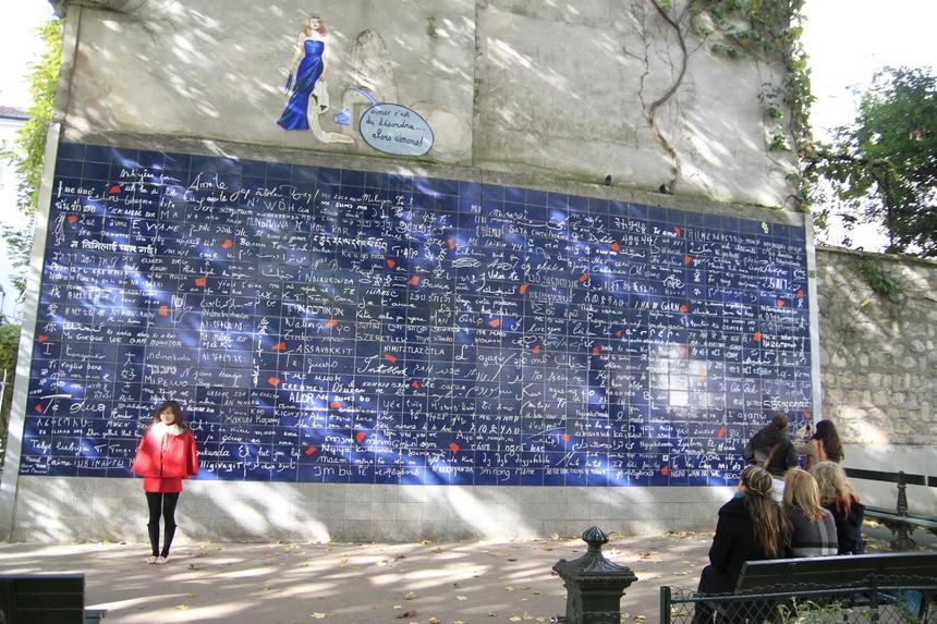 """Bức tường tình yêu đặt trong khu vườn Abbesses ở đồi Montmartre với diện tích 40 m2. Trên bức tường này, cụm từ """"I love you"""" được viết hơn 1.000 lần với hơn 300 ngôn ngữ khác nhau, phủ kín toàn bộ bề mặt bức tường. Dòng chữ """"Anh yêu em"""" được viết đầu tiên."""