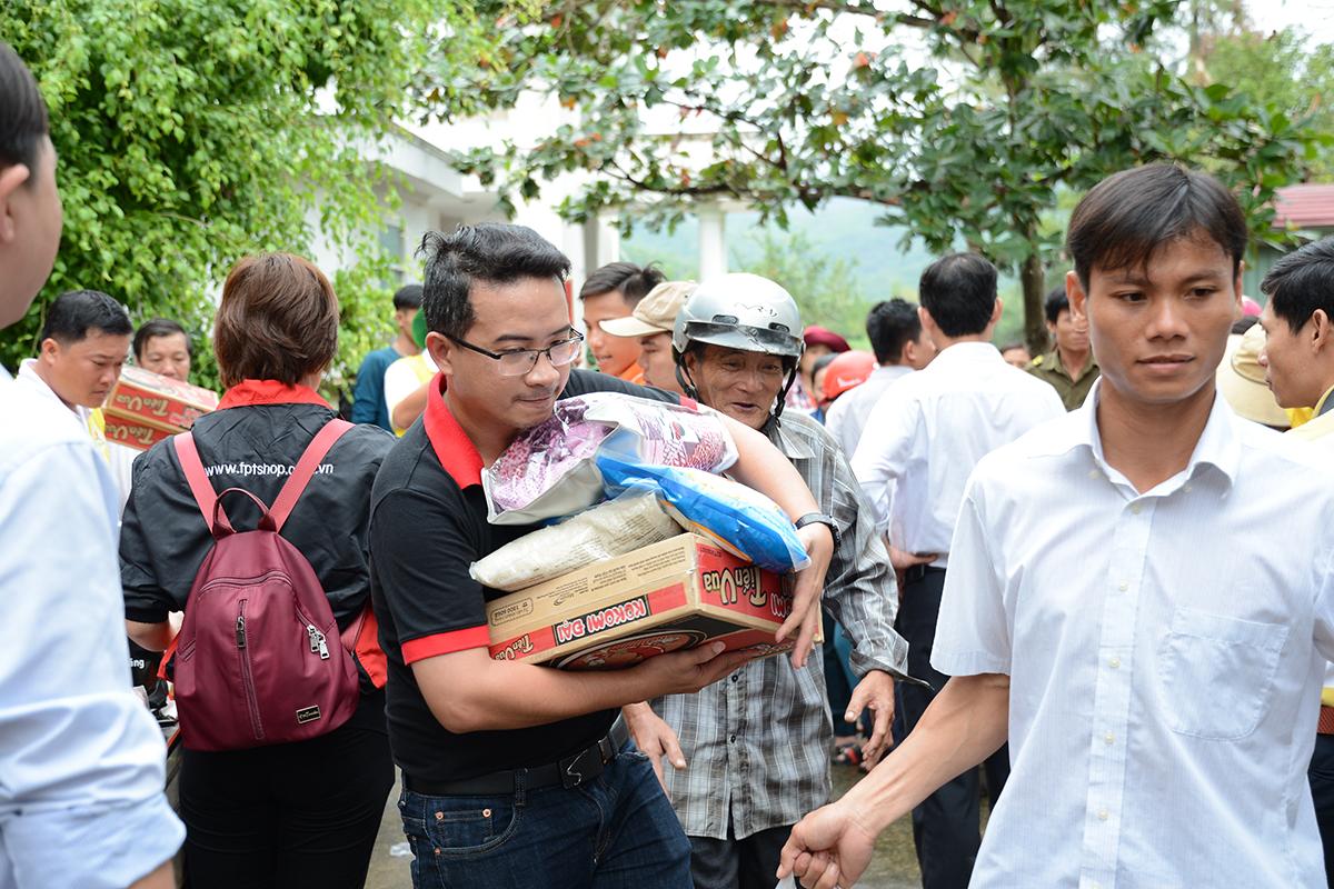 Vì phần lớn người cao tuổi đi nhận cứu trợ nên các thành viên trong đoàn thiện nguyện FPT hỗ trợ mang quà ra chỗ để xe.