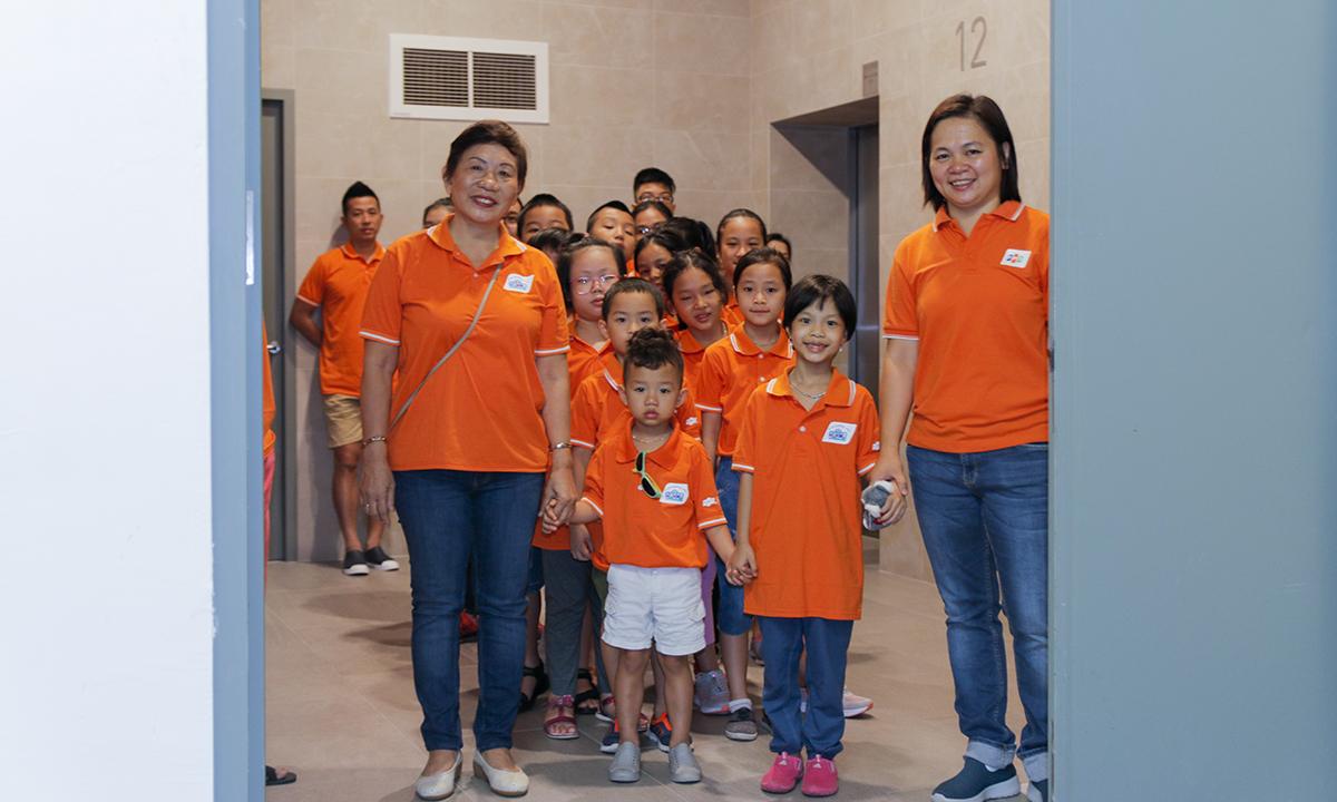 """Trưởng đoàn là """"bác Thanh""""- tên thân mật các bé và các phụ huynh gọi chị Trương Thanh Thanh, Giám đốc Trách nhiệm xã hội FPT. Chị Lại Hồng Điệp, Trung tâm dịch vụ sẻ chia (SSC) - FPT Asia Pacific (bên phải) dẫn đoàn tham quan."""