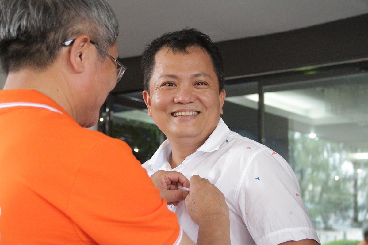 Anh Ngọc trao huy hiệu cho anh Lê Công Vinh, GĐ FPT IS Đà Nẵng. Dịp này, CEO FPT trao tổng cộng gần 1.000 áo đồng phục và huy hiệu FPT 30 năm cho CBNV tại Đà Nẵng.