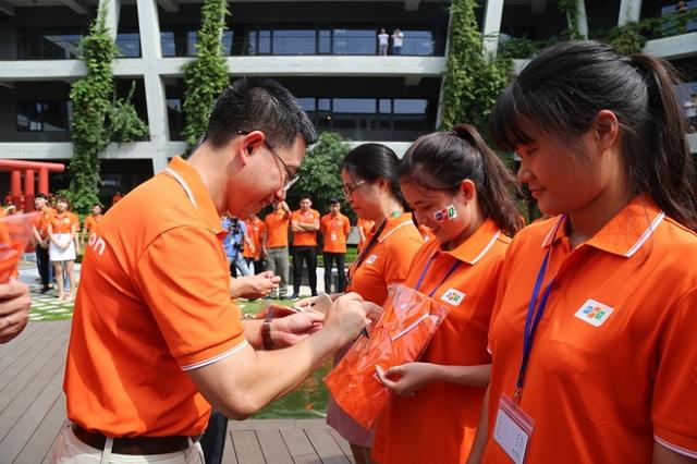 Các nữ nhân viên Phần mềm cười tươi khi được sếp cũ (anh Hoàng Việt Anh - nguyên TGĐ FPT Software, nay là PTGĐ FPT kiêm CEO Telecom) trực tiếp đeo huy hiệu.