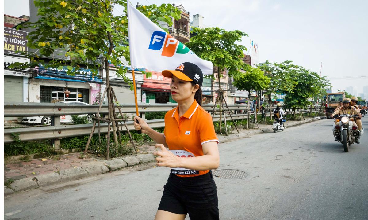 """Giám đốc FPT Telecom Hà Nội 4 - chị Hoàng Lan Hương, VĐV số áo 0266 đứng tại điểm chốt trên đường Giải Phóng, Hoàng Mai, Hà Nội, hào hứng chia sẻ: """"Tôi chưa bao giờ cảm thấy run và hồi hộp như lúc này. Trong người sục sôi một điều gì đó rất mạnh mẽ, tôi chỉ muốn nhận cờ và chạy thật nhanh để trao cho đồng đội kế tiếp. Là người FPT Telecom, tôi tự hào khi góp một phần sức lực của mình vào cuộc hành trình chạy từ Lạng Sơn đến Cà Mau""""."""