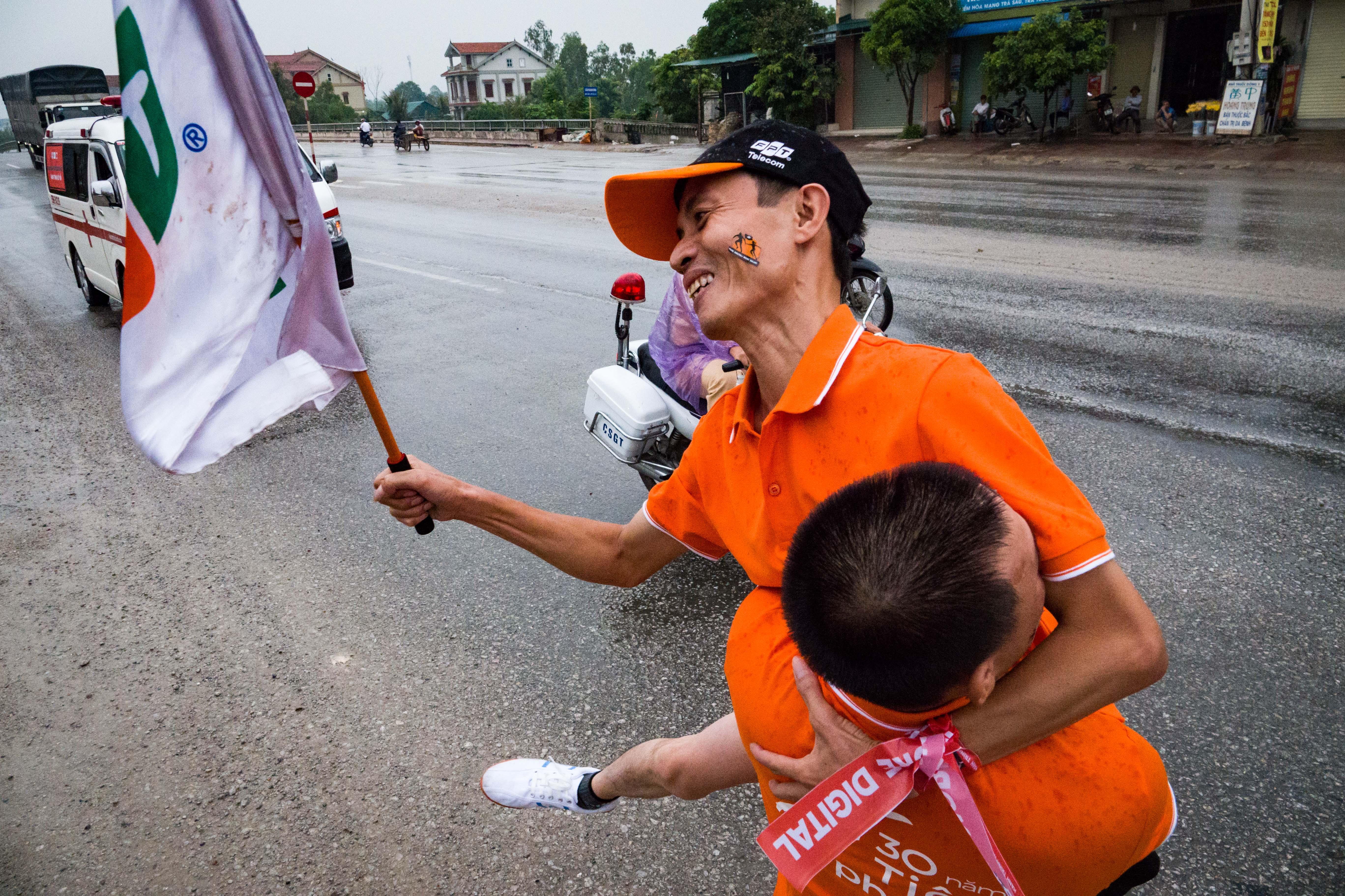 """Mang số thứ tự 614 là anh Hồ Khai Phong, vận động viên nhiều tuổi nhất tham gia giải chạy tiếp sức tại Nghệ An. Mặc dù có thân hình gầy gò nhưng anh Phong đã đăng ký chạy với quãng đường 1 km, nhiều hơn bình thường mà anh có thể chạy là 200 m. Về đích, trao cờ cho đồng đội, anh Phong ôm tiếp sức cho vận động viên số 615. """"Giá như được chạy nhiều hơn nữa thì tôi vẫn chạy được, nhưng quãng đường ngắn thì mỗi người góp sức một chút thế mới là tinh thần FPT"""", anh bày tỏ."""