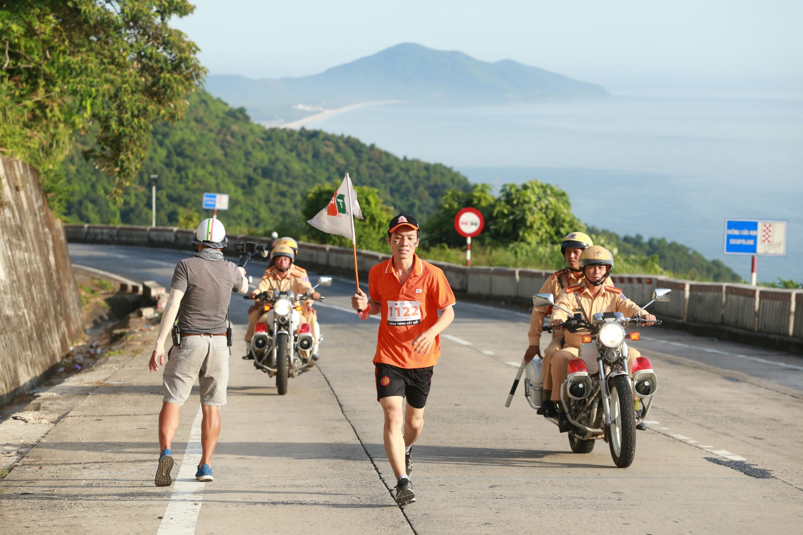 Nắng vàng rực rỡ tỏa sáng lá cờ FPT. Đường đèo dốc và dài khiến vận tốc của các vận động viên giảm đi đáng kể vì 1km đường đèo tương đương với 2km đường bằng phẳng bình thường.