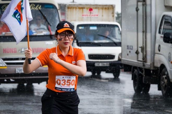 """Bóng hồng nhà """"Cáo"""" - Trịnh Thị Kim Cúc, FPT Telecom Hà Nam, là VĐV mang số áo 0350, cầm cờ FPT chạy trong cơn mưa nặng hạt tại Hà Nam, thu hút mọi ánh mắt của người tham gia giao thông."""