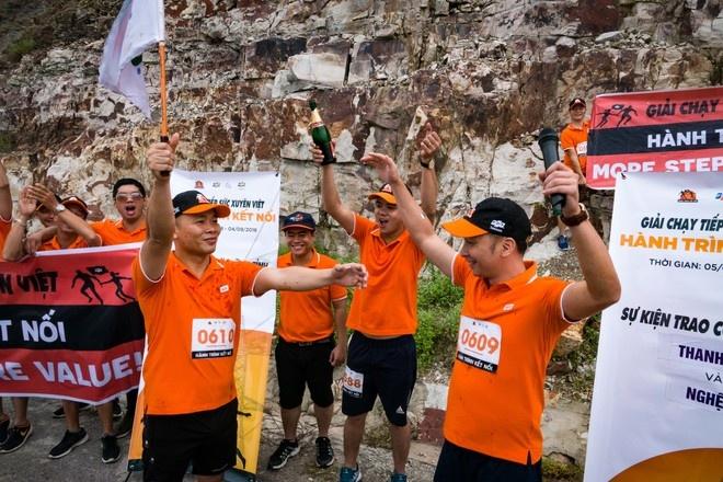 """Khoảnh khắc 2 VĐV nhà """"Cáo"""" trao nhau cờ FPT trong tiếng reo hò, vỗ tay cổ vũ của mọi người. Kết thúc chặng hành trình 94 km tại xứ Thanh, với 100 VĐV tham gia."""