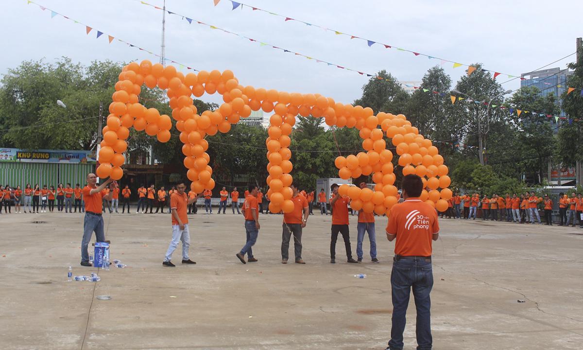 """Chữ """"FPT 30"""" được CBNV FPT Telecom Bình Dương kết từ bong bóng bay màu cam."""