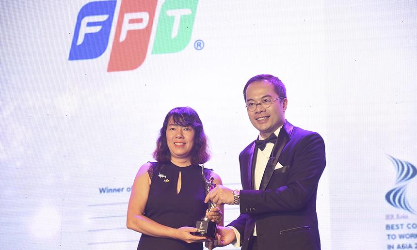 Trưởng ban Nhân sự FPT Trịnh Thu Hồng (trái) nhận Cup từ ông William Ng.