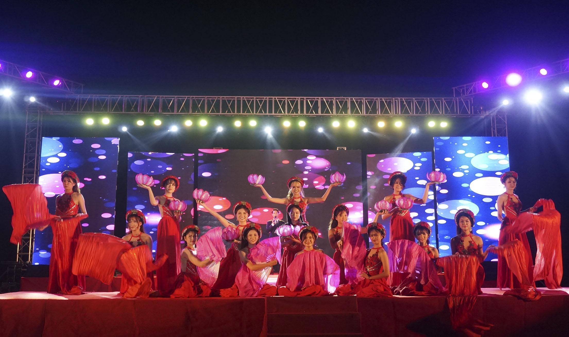"""Mở màn đêm thi là tiết mục múa dân gian trên nền nhạc """"Gấm"""" với sự góp mặt của chính 15 thí sinh xinh đẹp trong bộ đồ đỏ rực rỡ."""