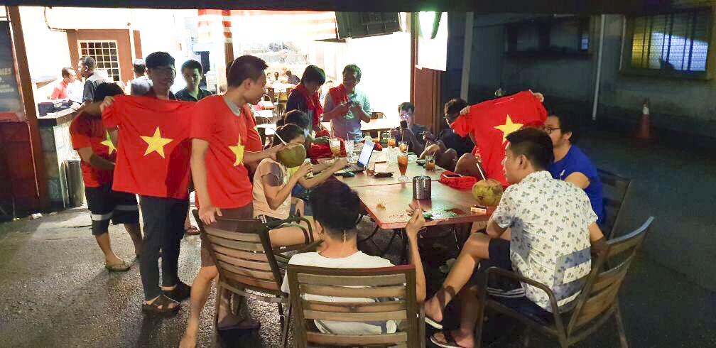 """BTC chuẩn bị áo và sticker từ tối hôm qua (10/12) cho từng thành viên. Rất nhiều người trong BTC đã có kinh nghiệm đi xem trận bóng """"lịch sử"""" ở sân Bukit Jalil vào 4 năm trước nên đã cùng nhau đưa ra những """"tip"""" nhỏ để giữ an toàn sau trận đấu. Trong đó có một chia sẻ vừa thật vừa hài hước: """"Nếu tuyển Việt Nam thắng thì hãy cố gắng cười ít thôi, thậm chí sầu não như vừa thất tình. Trong trường hợp xấu nhất, hãy hét thật to để đồng hương nghe thấy. Dù sao cũng chỉ bị đấm mấy cái vớ vẩn ấy mà""""."""