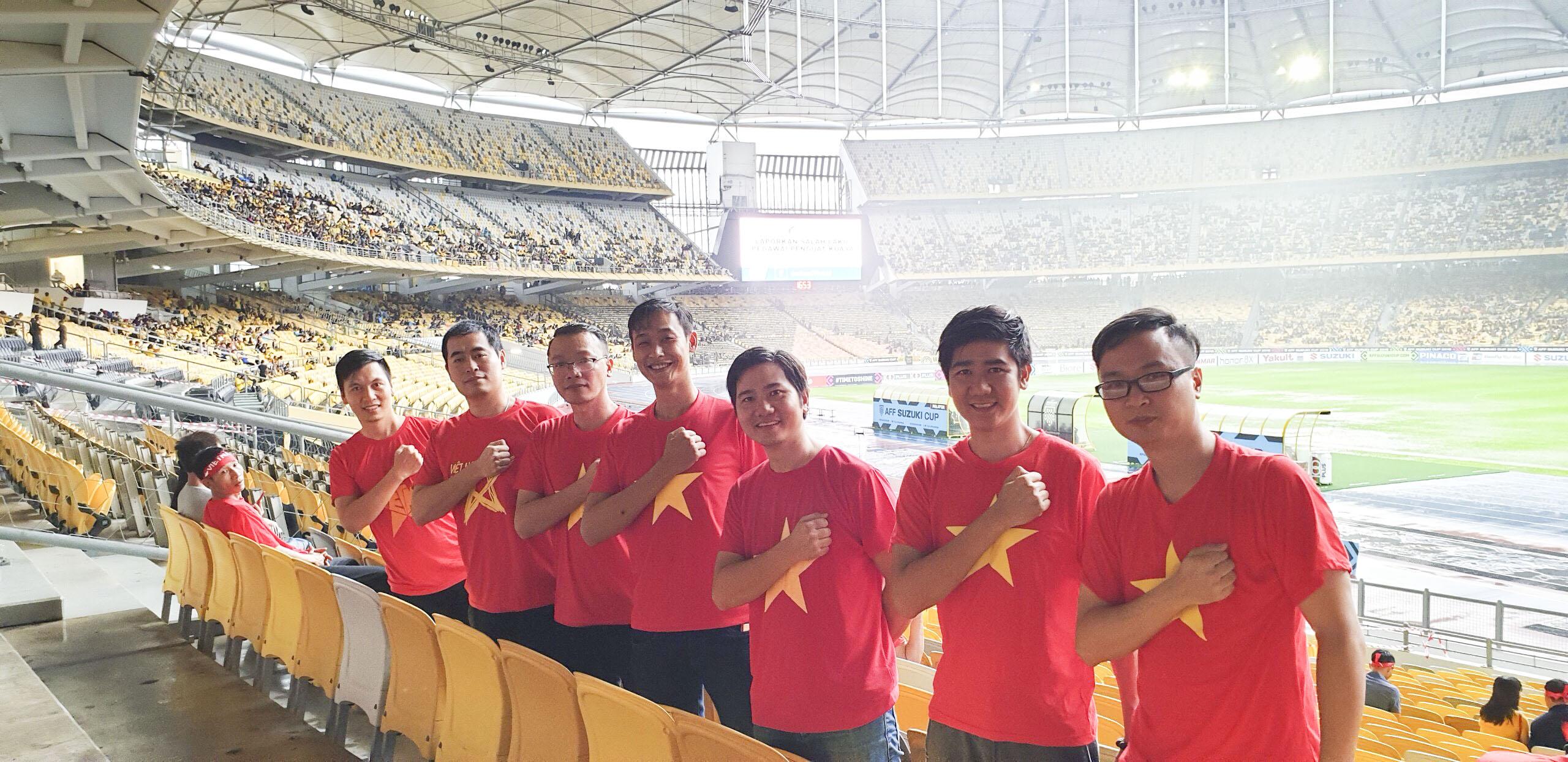 """Bên cạnh các FMAS, nhà F Việt Nam cũng có các CĐV đã bay sang Malaysia để cổ vũ cho đội nhà. Anh Vũ Chí Thành - Giám đốc FPT Polytechnic - là một trong những người có mặt ở Bukit Jalil từ rất sớm. Nói về trận chung kết lượt đi, anh Thành đánh giá đây là một khó khăn thực sự của đội tuyển Việt Nam: """"Trận hôm nay rất căng, Malaysia đá sân nhà rất tốt, nhưng khả năng sẽ là trận hòa có bàn thắng hoặc Việt Nam thắng chênh một bàn. Tôi nghĩ Trọng Hoàng sẽ ghi bàn và tỏa sáng"""". Trong ảnh là các thành viên của FPT Polytechnic Hà Nội, TP HCM, Đà Nẵng, Đăk Lăk và Cần Thơ."""