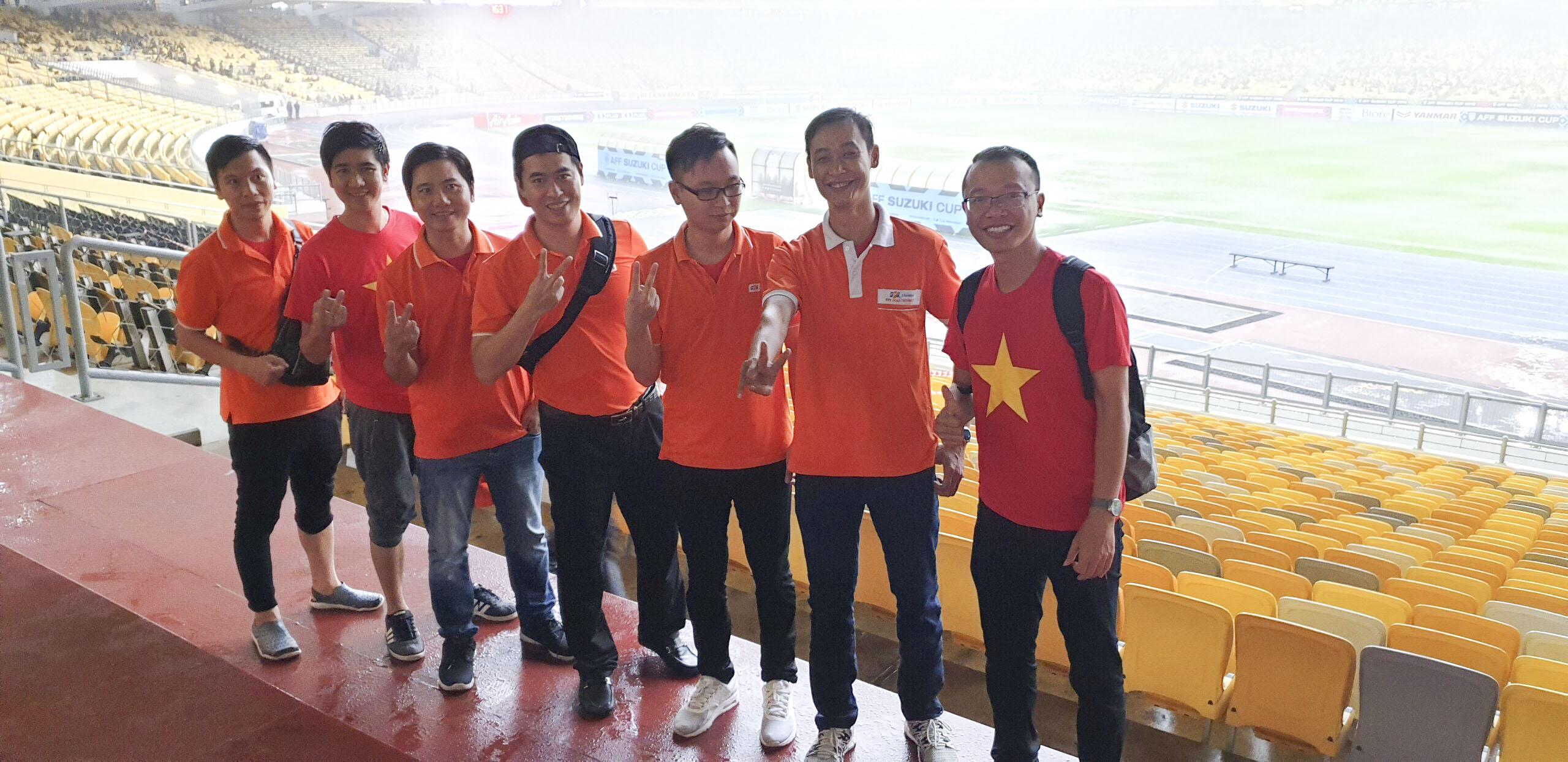 """Một thành viên khác của FPT Polytechnic là anh Dương Đình Cường (ngoài cùng bên phải) cho biết anh đã phải nhờ một người bạn ở FMAS mua vé từ rất sớm để có được vị trí đẹp trên sân hôm nay. """"Tôi đã xem hầu hết các trận thi đấu của Malaysia. Đây là đội có lối chơi cực kỳ rắn và đầy quyết tâm. Sẽ là thế trận đội chủ nhà dồn ép chúng ta, tuy nhiên với chiến thuật của HLV Park như hiện tại, Việt Nam càng bị dồn ép thì đá phản công càng hay. Tôi rất tin tưởng vào tâm lý của họ. Chảo lửa 90.000 khán giả ở Bukit không thể gây áp lực cho chúng ta mà còn tạo động lực và cảm giác hưng phấn cho đội tuyển. Về kết quả trận đấu, tôi nghĩ Việt Nam sẽ có chiến thắng với cách biệt 1 bàn""""."""