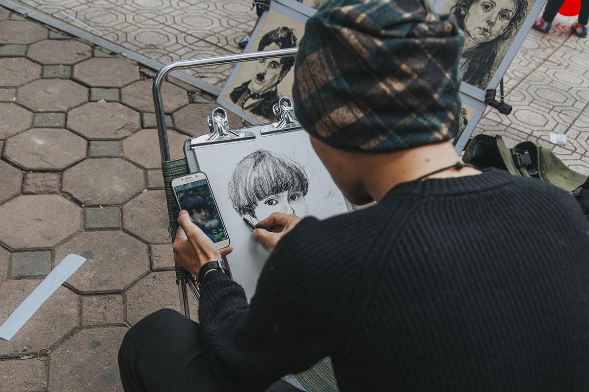 """Người họa sĩ đường phố cũng không quên """"trùm kín"""" để chống chọi cái lạnh, lặng lẽ vẽ tranh bên góc Hồ Gươm."""