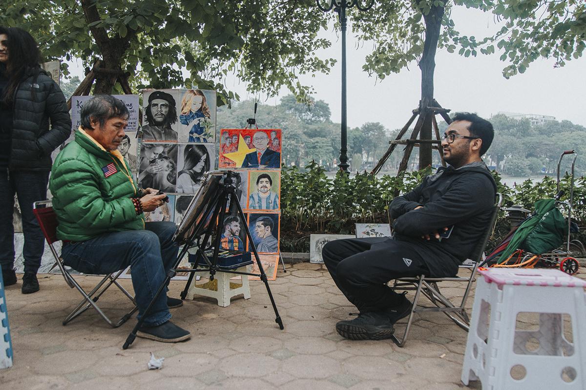 Một du khách nước ngoài tỏ ra thích thú khi ngồi làm mẫu tranh chân dung nhưng vẫn tỏ ra co ro trong cái rét đậm.