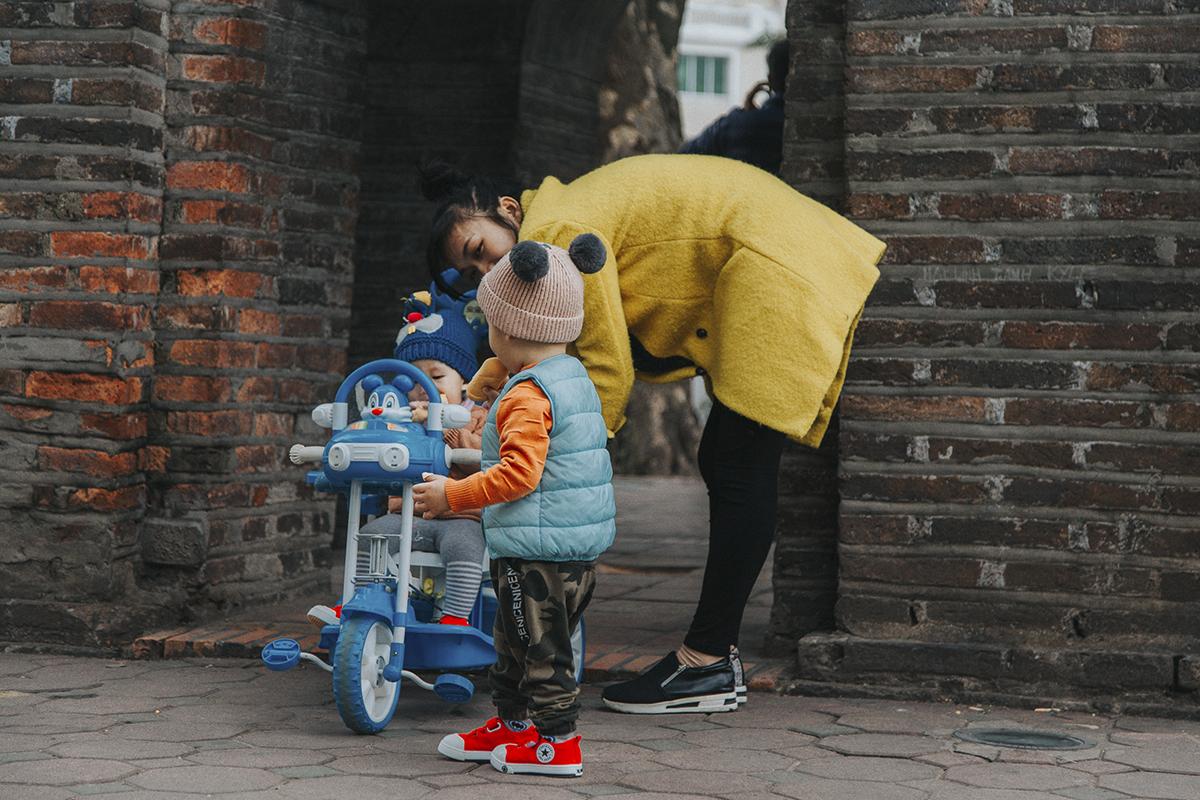 Những em bé được bố mẹ dắt đi dạo trên phố đi bộ sau khi đã trang bị những chiếc áo ấm dày và che kín từ đầu đến chân.