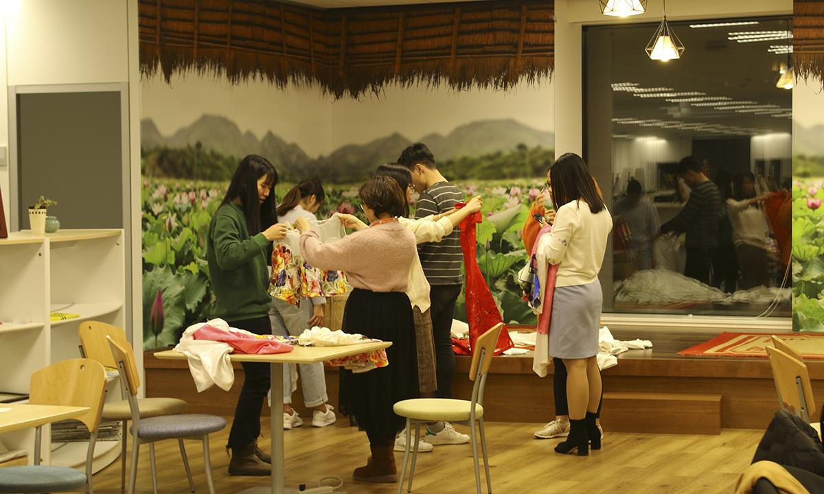 Các diễn viên xem và thử trang phục phục vụ trong vở diễn.