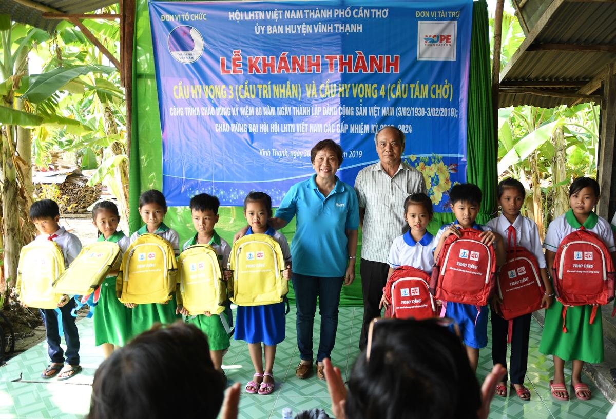 Chị Trương Thanh Thanh và anh Hoàng Công (nguyên Trưởng ban Nhân sự FPT IS, đại diện gia đình bác Hoàng Công Tâm, nhà tài trợ xây cầu Hy Vọng 4) tặng đồ dùng học tập cho trẻ em nghèo xã Thạnh Mỹ nhân dịp xuân về.