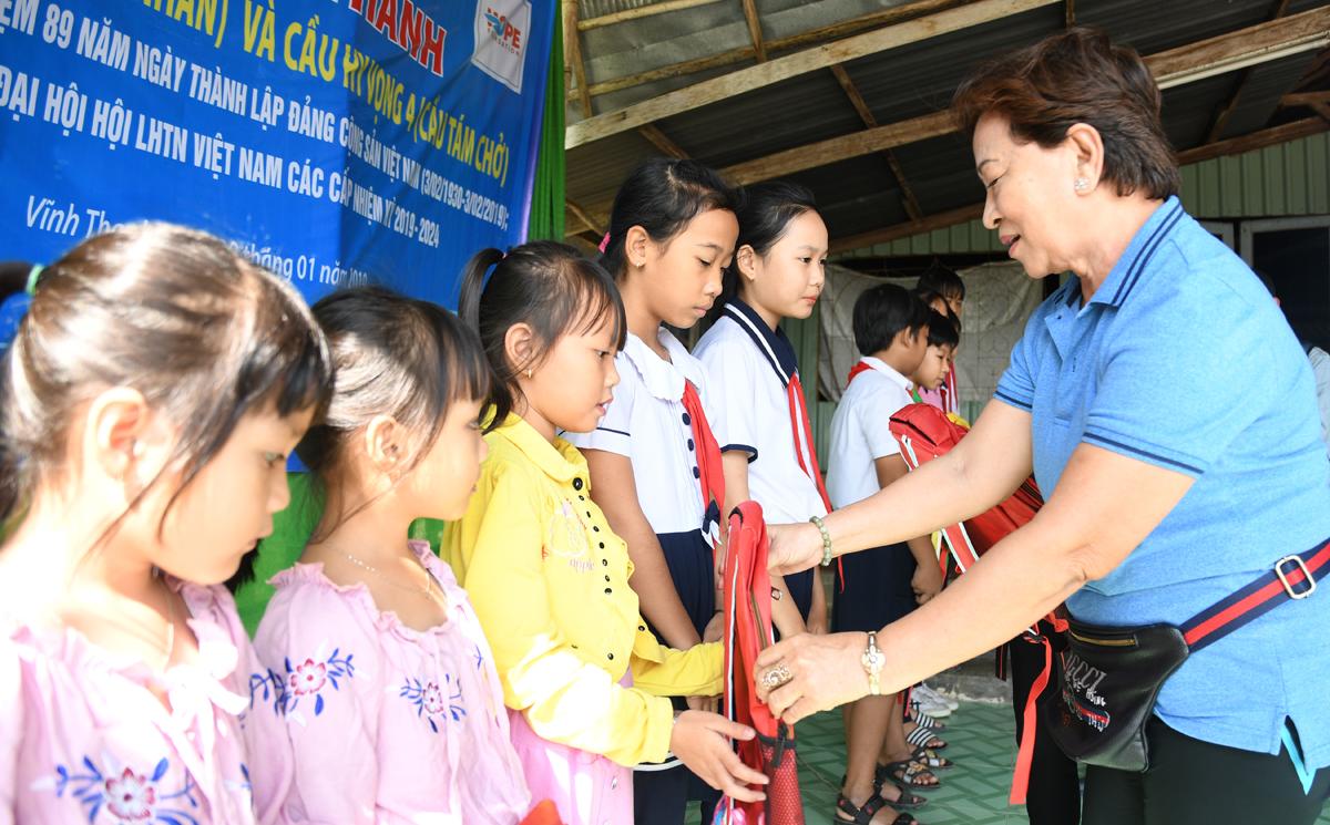 Đại diện nhóm hồ bơi Phú Thọ - một trong những nhà tài trợ xây cầu mới của Quỹ Hy vọng cũng tặng trẻ em nghèo hiếu học địa phương những phần quà và lì xì năm mới.