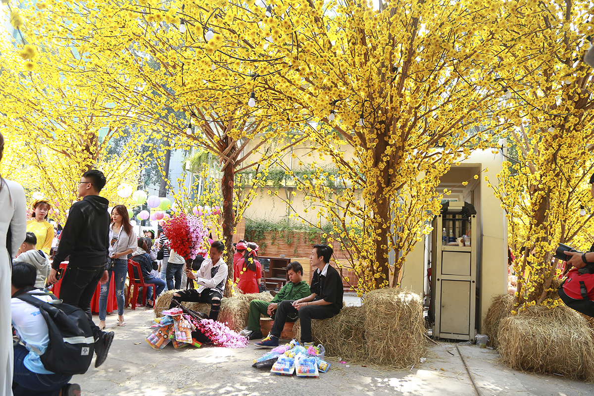 Tranh thủ nhu cầu chụp ảnh đầu xuân của khách tham quan, nhiều người còn mở dịch vụ bán hoa mai - đào giả, bao lì xì, heo đất, máy tạo bong bóng,...