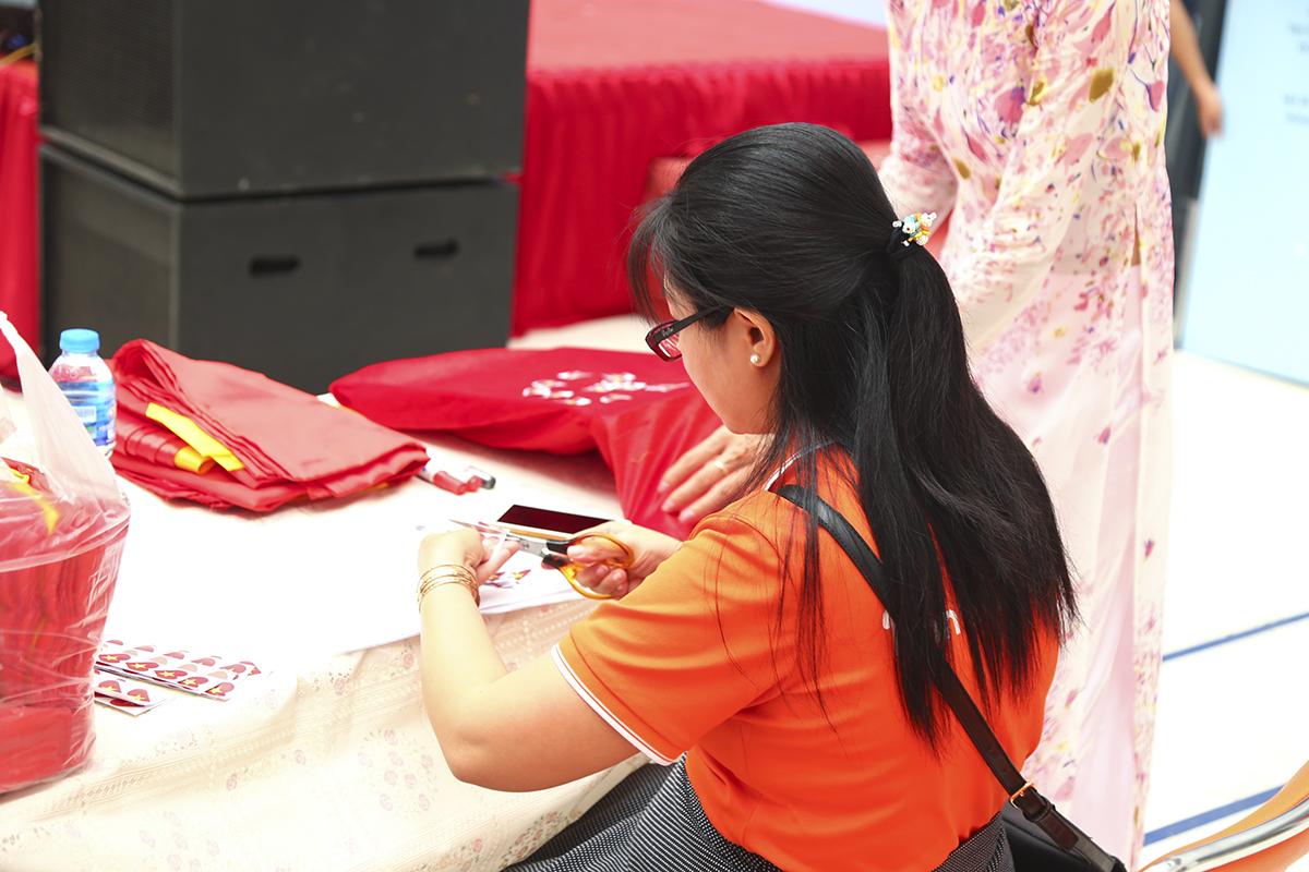 Bên cạnh sân khấu, chị Nguyễn Đặng Bình An, Chủ tịch công đoàn Synnex FPT Cần Thơ, cẩn thận cắt rời từng chiếc sticker in hình lá cờ Việt Nam để các thành viên nhà F chuẩn bị dán lên tấm bản đồ.