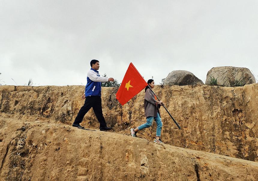 Chị Hồ Thị Ngọc Hiếu, Ban Văn hóa - Đoàn thể FPT tại Đà Nẵng, cầm lá cờ tổ quốc vượt qua những ngọn đồi để đến với các hộ dân bị chia cắt.