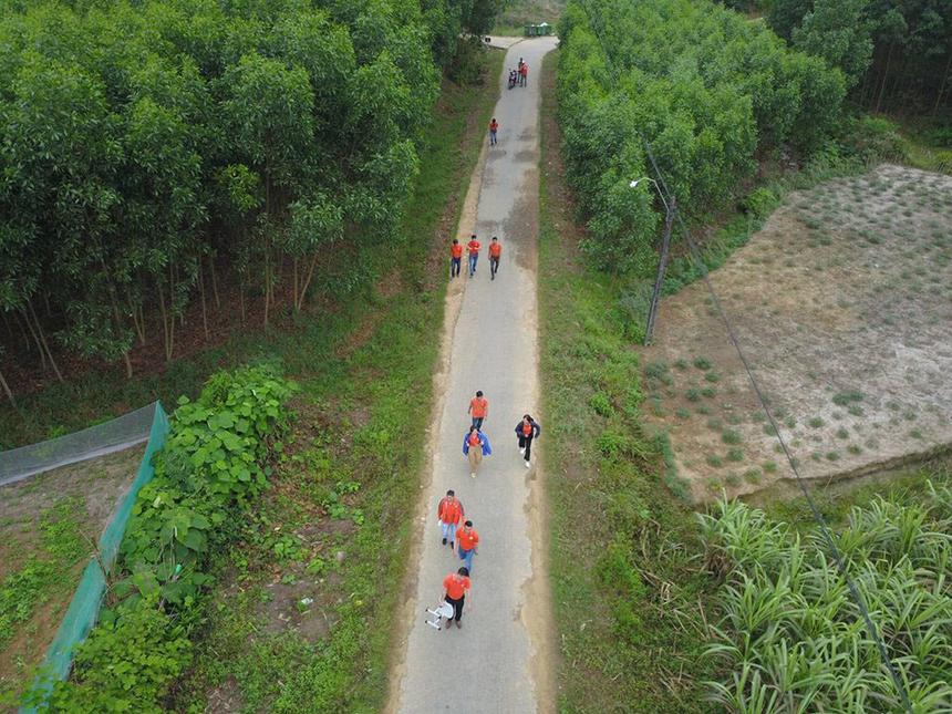 Dòng người áo cam di chuyển trên những cung đường làng để đến với gia đình các học sinh.