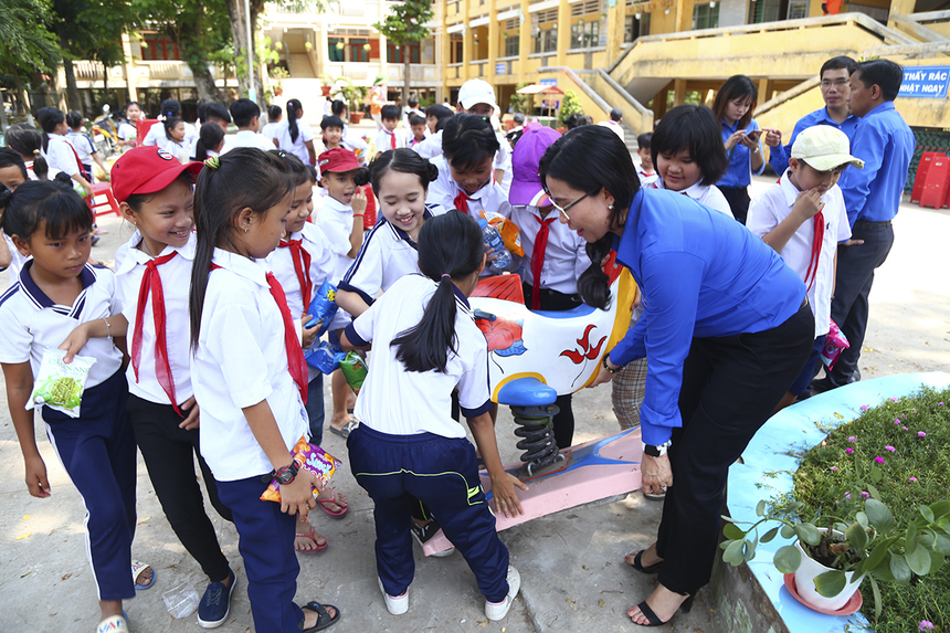 Chị Nguyễn Phạm Duy Trang - Phó Chủ tịch Hội đồng Đội Trung ương cùng các em thiếu nhi bê chiếc thú nhún ra giữa sân trường sau khi hoàn tất thủ tục trao tặng Công trình Măng non.