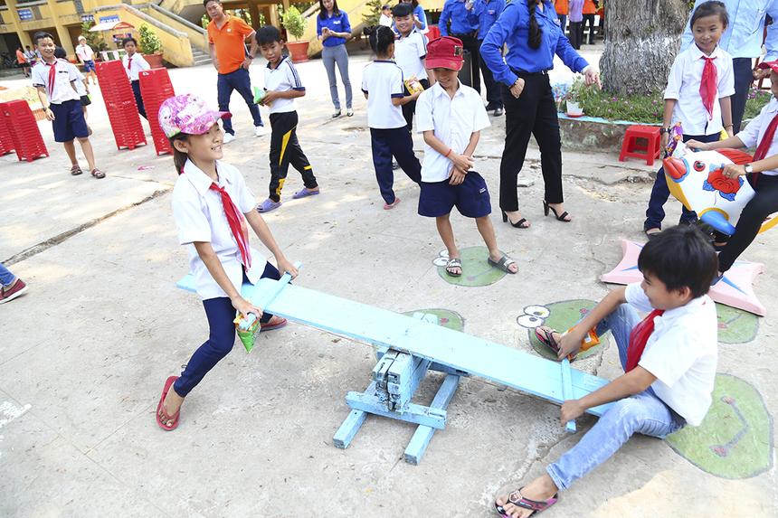 Ở một góc sân trường khác, hai em bé đang thi nhau chơi trò bập bênh với chiếc cầu được đóng chắc chắn bằng ván gỗ.
