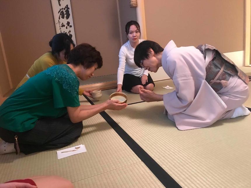 Giảng viên giải thích cho học viên về những hoa văn in trên cốc trà. Mỗi loại hoa văn đều có ý nghĩa riêng của nó và khi đón trà từ tay người tiếp trà thì cần phải xoay cốc sao cho đúng quy tắc của Trà đạo. Trà đạo được xem như là một điển hình văn hóa cổ xưa của Nhật Bản, được phát triển từ khoảng cuối thế kỷ XII. Theo truyền thuyết Nhật, ngày đó có vị cao tăng người Nhật là Eisai (1141-1215) đi du học và mang về từ Trung Quốc một loại bột trà xanh được gọi là matcha. Lúc đầu matcha chỉ được dùng như một loại thuốc nhưng sau đó trở thành một thức uống xa hoa mà chỉ giới thượng lưu mới được sử dụng và thưởng thức trong các buổi họp mặt.
