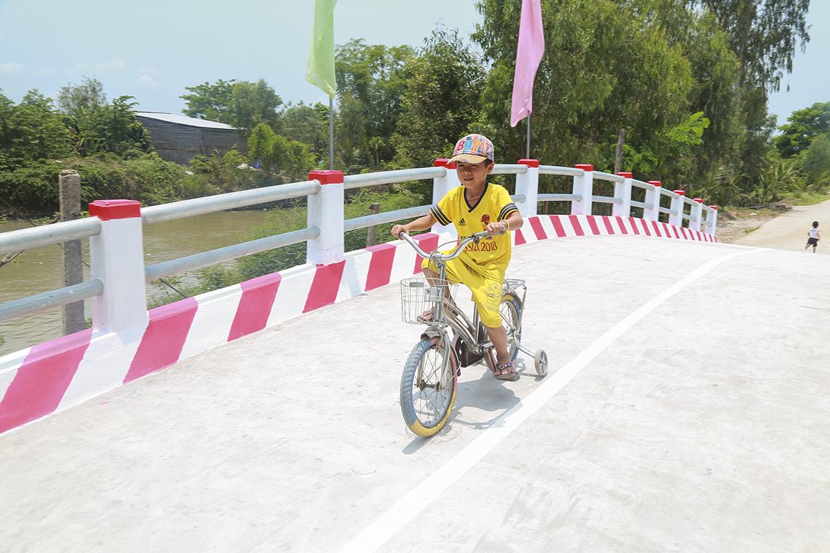"""Dẫn đứa con ra xem cây cầu mới vừa khánh thành, anh Nguyễn Văn Cột mừng vui khôn xiết: """"Làm được cây cầu cho bà con, các cháu qua lại, tôi vui lắm. Mấy chục năm nay đâu có niềm vui lớn như thế này, từ cầu gỗ giờ bắt cây cầu bê tông dễ gì có được, mừng không biết nói sao cho hết""""."""