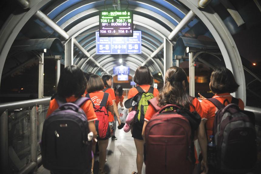 Các bóng áo cam lần lượt qua cổng check-in để chờ tới giờ tàu chuyển bánh.