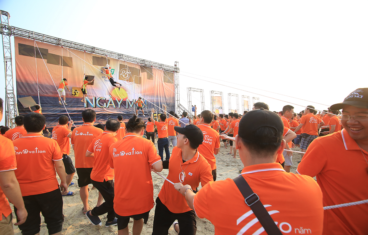 """Trên tấm phông lớn dựng giữa bãi biển Cảnh Dương hiện ra """"OKR"""" lớn của nhà Hệ thống: mỗi người Việt Nam dùng ít nhất 1 phần mềm của FPT IS. CEO Nguyễn Hoàng Minh hy vọng với niềm tin trong Hành trình Ngày mới này, nhà Hệ thống sẽ đạt đc những gì kỳ vọng, hiện thực hoá kế hoạch đặt ra cho 3 năm tiếp theo này."""