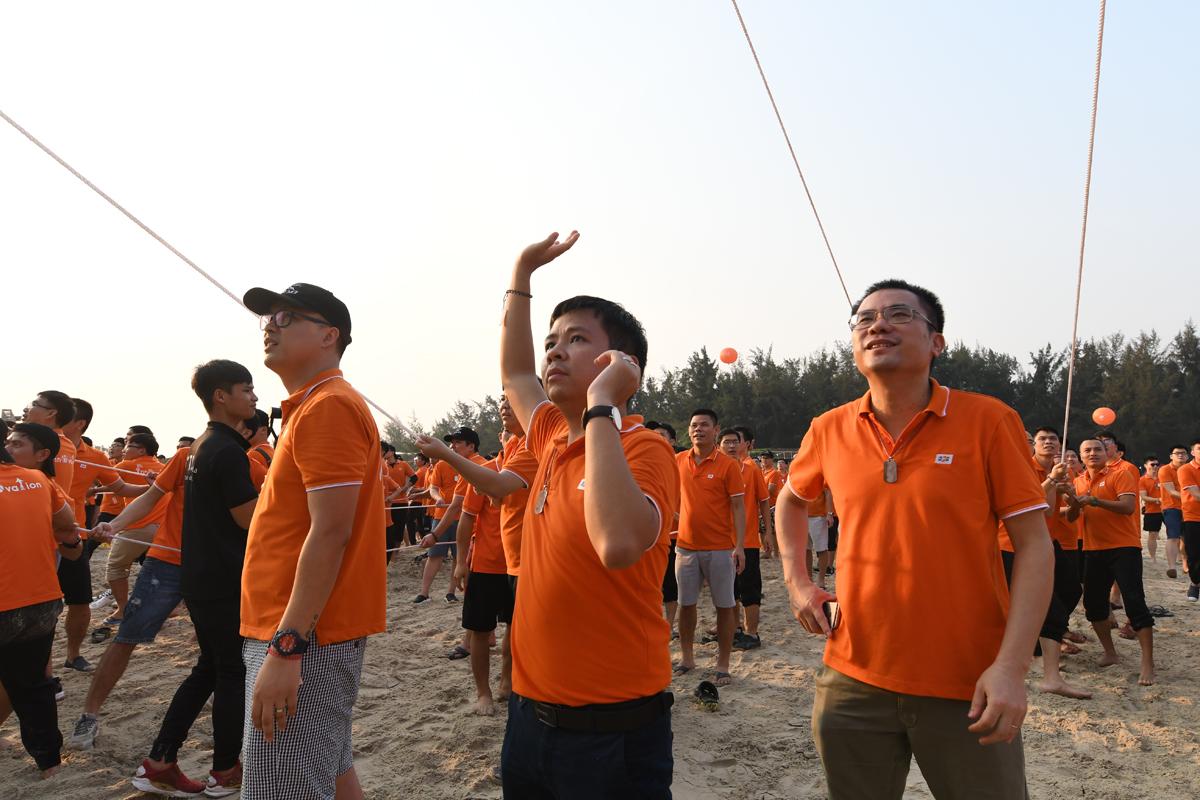 """Chủ tịch FPT IS Dương Dũng Triều không rời mắt khỏi các CBNV đang treo người trên cao để ghép hình cho tấm phông lớn. Anh rất vui mừng khi chứng kiến tinh thần hăng hái, máu lửa của người nhà Hệ thống trong tất cả phần mục của """"Hành trình Ngày mới""""."""