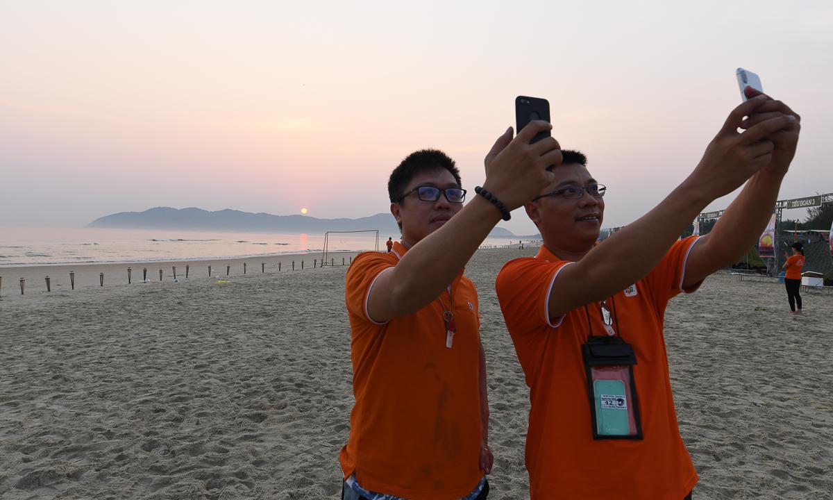 """Sáng sớm, mặt trời như quả cầu lửa nhô lên từ biển Ðông. Anh Nguyễn Duy Hiền (phải) - FPT IS GMC - cho biết đây là lần đầu tiên anh chứng kiến cảnh mặt trời mọc sau rặng núi. """"Không ngờ mặt trời mọc khá nhanh. Tôi đã quay lại hết cảnh từ lúc mặt trời ló và ra khỏi rặng núi"""". Anh thú nhận trước đây đi biển nhiều và """"lúc nào cũng xác định dậy sớm xem bình minh nhưng chưa bao giờ xem được"""", nhất là lại cùng một 2.000 người FPT IS mặc áo cam"""