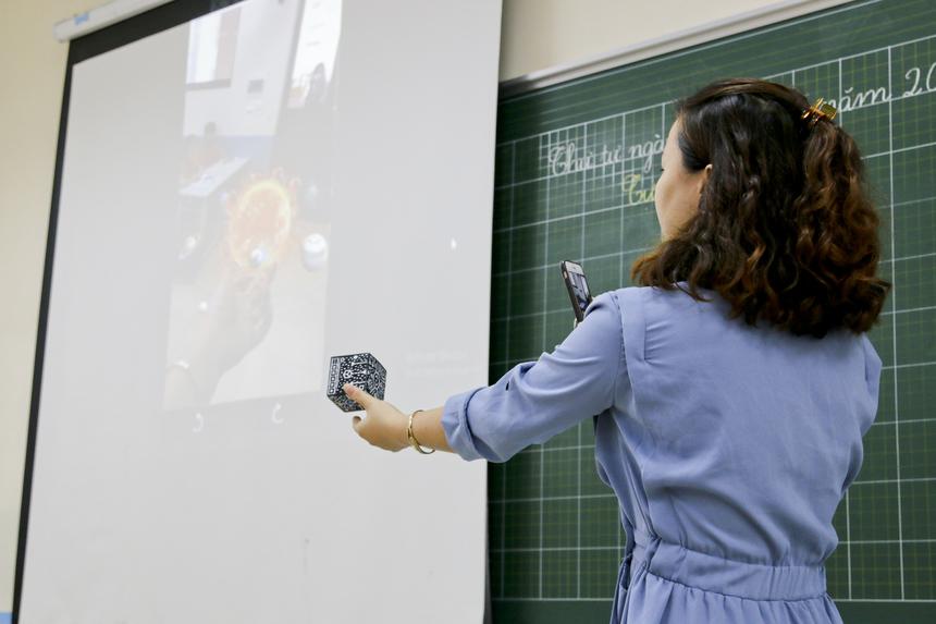 """Trong bài giảng, cô giáo sử dụng các công cụ được chuẩn bị sẵn để ứng dụng công nghệ thực tế ảo. Đó là môi trường không gian ba chiều được giả lập bằng máy tính nhằm mô phỏng lại thế giới thực. Nhờ đó có thể trình bày dữ liệu phức tạp theo cách trực quan, dễ tiếp cận. Học sinh có thể tương tác với các đối tượng trong môi trường ảo để khám phá sâu hơn về chúng, có thể hiểu bài và ghi nhớ sâu hơn. Với môn """"Khoa học và Xã hội"""", học sinh được tìm hiểu hệ mặt trời bằng cách quan sát tiến trình hoạt động của các ngôi sao trong không gian ba chiều, tương tác vật lý như """"di chuyển"""" các hành tinh trong vũ trụ ảo. Trong ảnh: Hình ảnh hệ mặt trời hiện lên trên màn hình chiếu khi cô Lan sử dụng công nghệ thực tế ảo."""