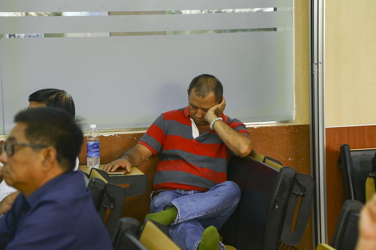 Một phụ huynh đưa con đi thi chợp mắt trong thời gian chờ con làm bài thi. Với những gia đình ở các tỉnh lân cận TP HCM như Long An, Bà Rịa - Vũng Tàu, thí sinh phải đến từ rất sớm để kịp check-in nhận phòng thi.