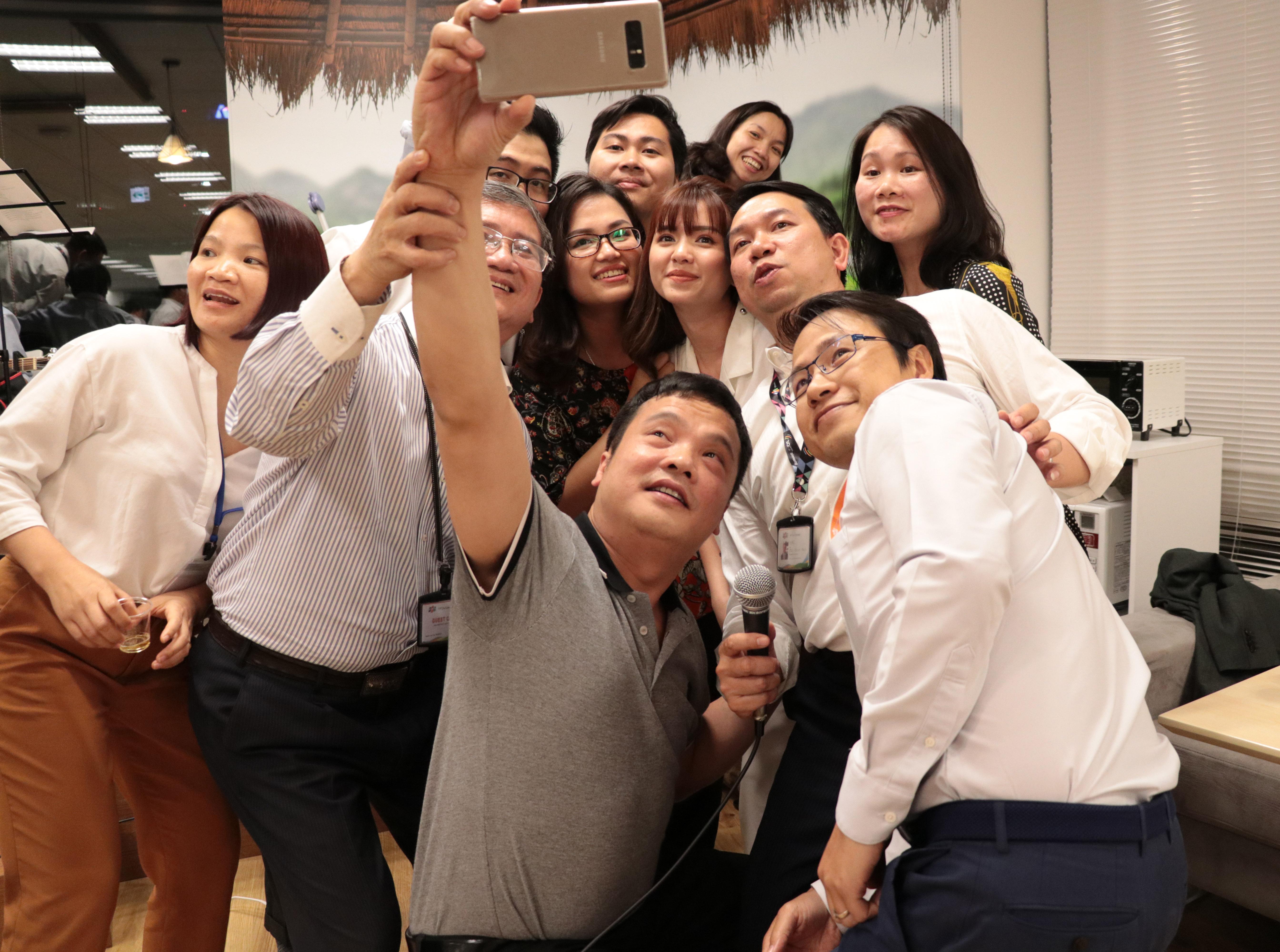 Phó Chủ tịch FPT Bùi Quang Ngọc đỡ tayCEO FPT Nguyễn Văn Khoa chụp hình bằng chính điện thoại của anh.