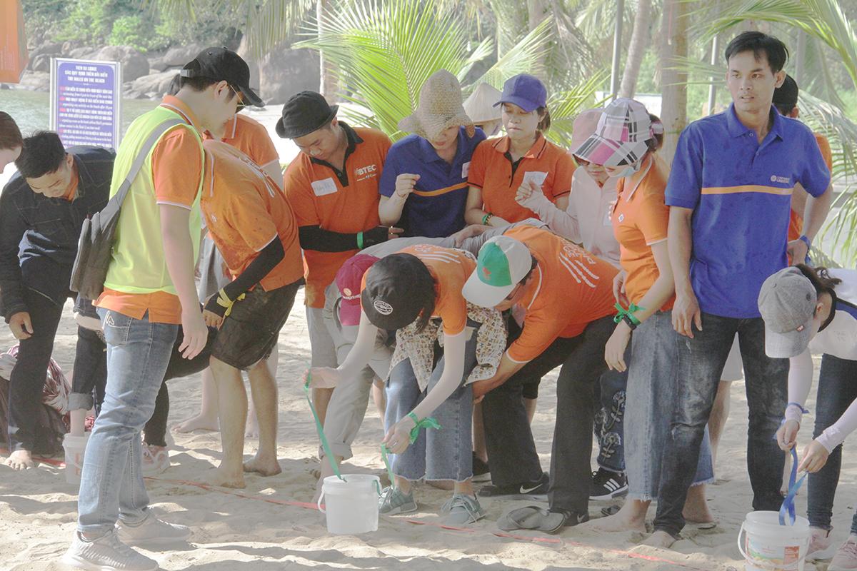 """Nhiệm vụ đầu tiên trong trò chơi là các đội phải """"Khiêng nước về làng"""". Học viên dùng tay điều khiển dây và ly nhựa để di chuyển nước về địa điểm tập kết."""
