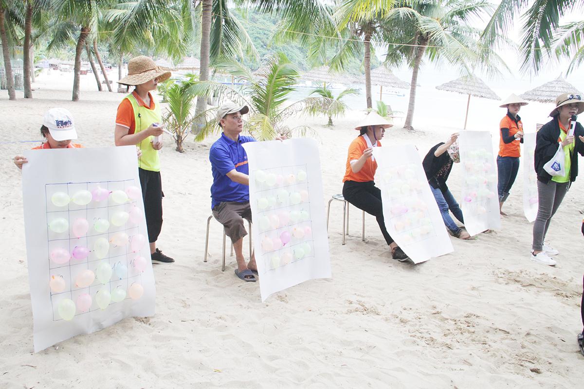 5 thành viên cầm giấy ngồi thành hàng ngang. Mỗi bong bóng vỡ sẽ tương ứng với số điểm được ghi trước đó.